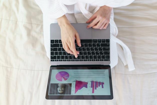 女性は自宅で仕事します。バスローブの女性は家にいます。ラップトップまたはオンラインショッピングで動作します。