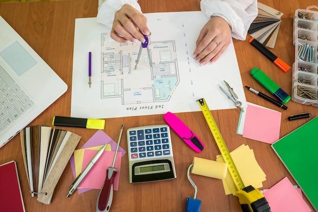 女性はオフィスで働く-家の計画とラップトップ