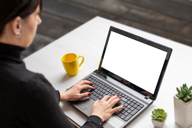 Woman work on laptop with isolated screen on white flat desk with cup of coffee and plants