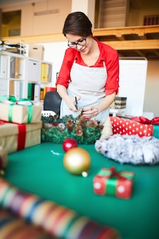 Woman at work, making a christmas wreath and wrapping gifts