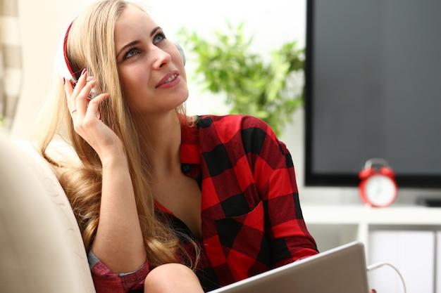 노트북에서 일하는 여성은 음악 헤드폰을 듣습니다.