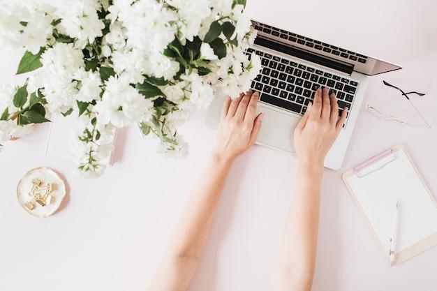 女性はラップトップで動作します。ピンクのテーブルにコンピューター、花の花束、文房具を備えたオフィスデスクワークスペース