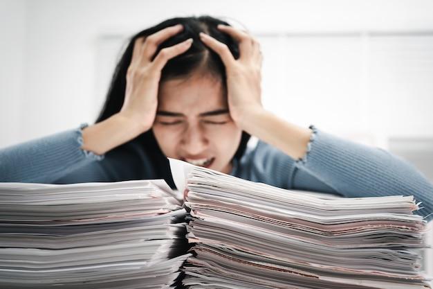 テーブルの上の紙の山で忙しい女性の仕事のストレスユーモア