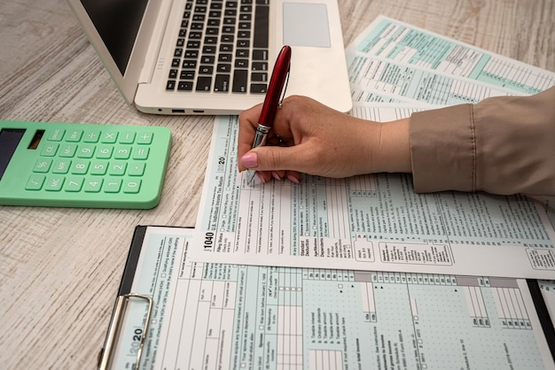 여성은 미국 세금 양식 1040과 사무실에서 계산기 노트북으로 일합니다. 회계 개념