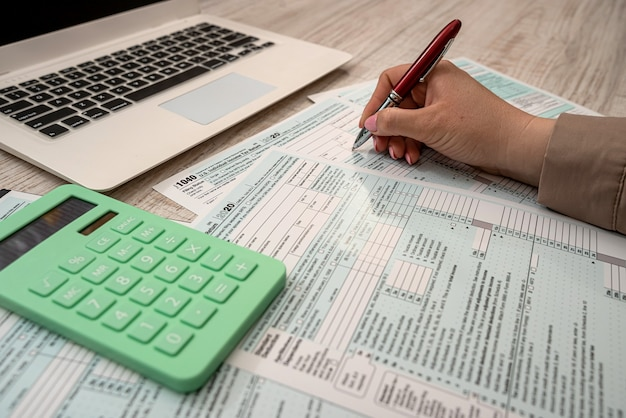 Woman work with usa tax form 1040 and calculator laptop at office. accounting concept