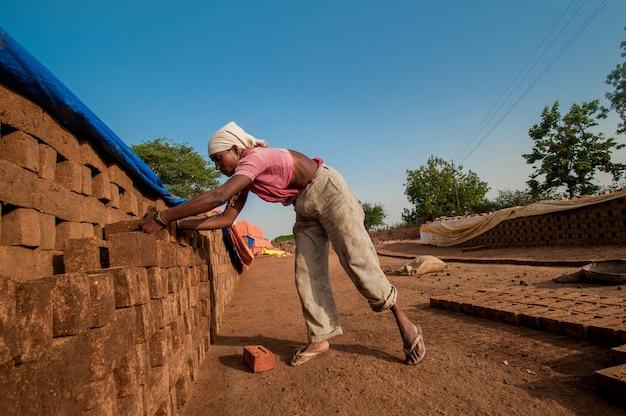 女性労働者はレンガ工場で次のプロセスのためにレンガを配置します