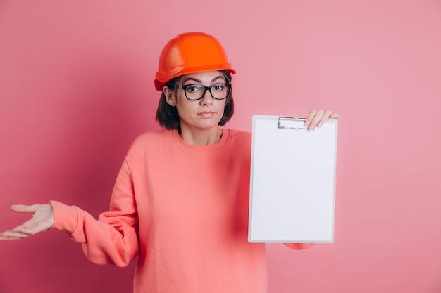 Il costruttore del lavoratore della donna tiene il bordo bianco del segno in bianco contro fondo rosa. casco da costruzione. femmina alzando le mani e alzando le spalle, senza avere la minima idea