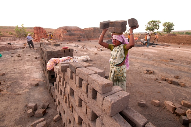レンガ工場で次のプロセスのためのレンガを運ぶ女性労働者