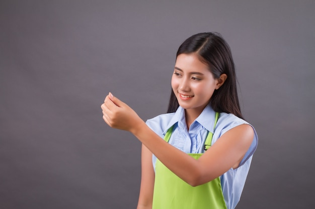 Woman worker hand up holding something on blank space