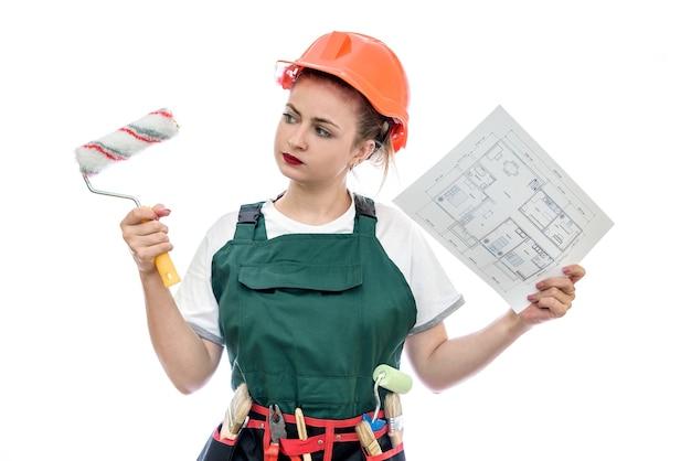 Женщина-работник держит план дома и ролик, изолированные на белой стене