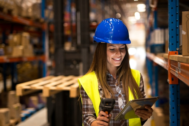 Woman worker holding tablet and bar code scanner checking inventory in large distribution warehouse
