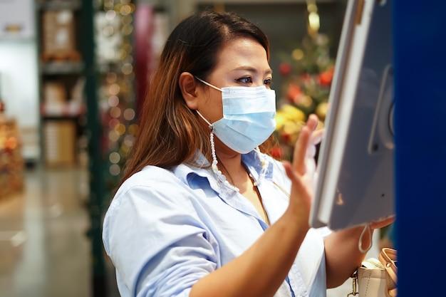 大規模な倉庫で働いている間、製品の在庫を検査する女性労働者。