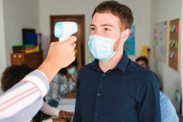 현대 사무실에서 동료의 체온을 측정하는 여성 노동자-남자 얼굴에 초점