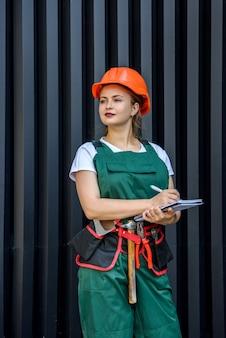 女性労働者またはビルダー。暗い背景に対してポーズをとってつなぎ服とヘルメットの美しい女性