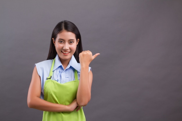 Woman worker pointing thumb up, presenting something on blank space
