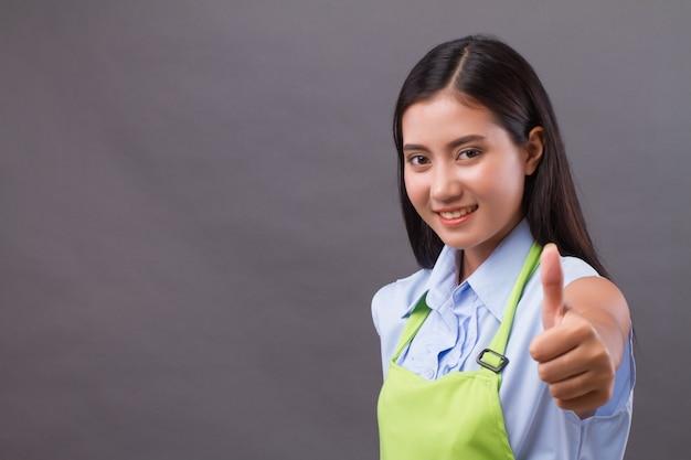 親指を上に向けて、空白のスペースに何かを提示する女性労働者