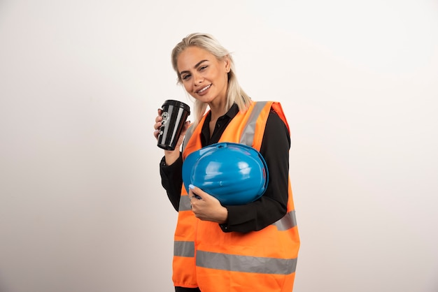 Lavoratore donna in posa con una tazza di caffè su sfondo bianco. foto di alta qualità