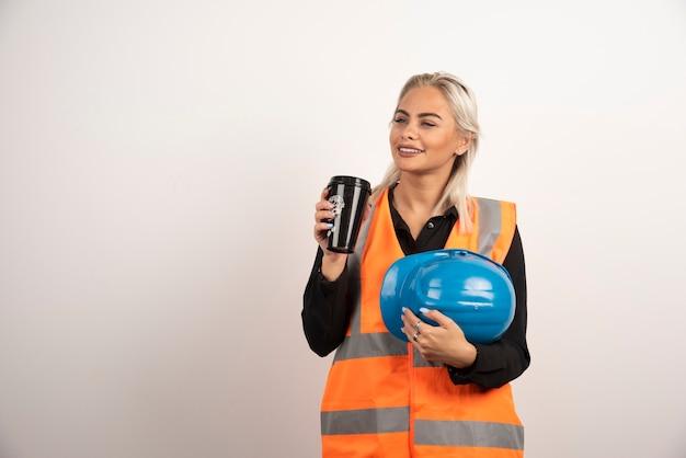 Работник женщины представляя с чашкой кофе на белой предпосылке. фото высокого качества
