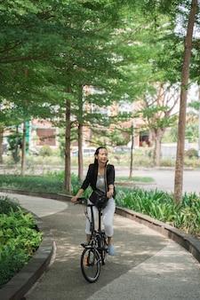 折りたたみ自転車に乗る準備ができている女性労働者