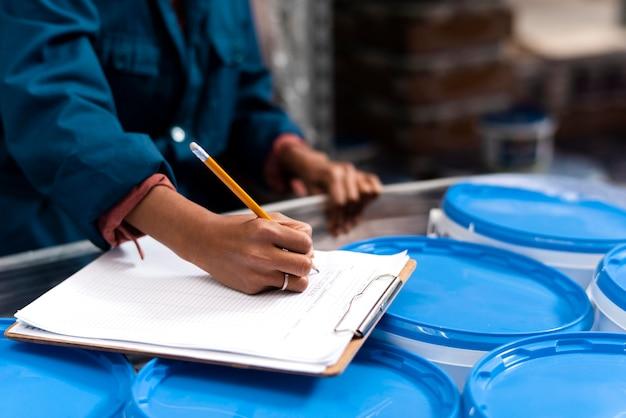 Женщина-работник делает заметки на складе