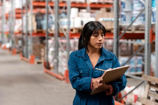창고에서 메모를 하는 여성 노동자