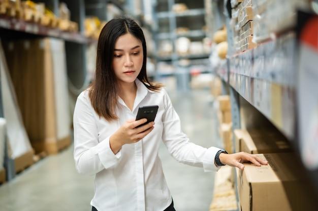 창고 매장에서 재고를 확인하기 위해 스마트 폰을 사용하는 여성 인부