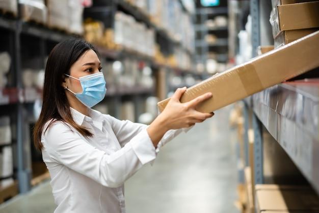 코로나 바이러스 전염병 동안 창고에서 재고를 확인하는 의료 마스크가있는 여성 노동자