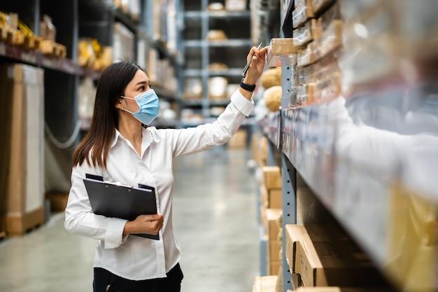 의료 마스크 클립 보드를 들고 코로나 바이러스 전염병 동안 창고에서 재고를 확인하는 여성 노동자