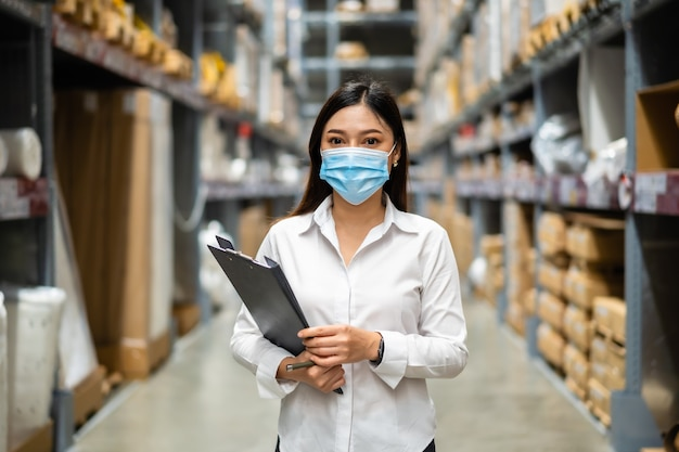 Woman worker with medical mask holding clipboard and checking inventory in the warehouse during coronavirus pandemic