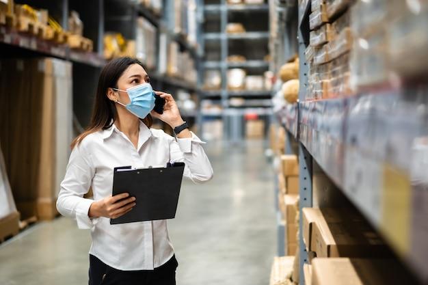의료 마스크가 휴대 전화로 이야기하고 클립 보드를 들고 여성 노동자가 코로나 바이러스 전염병 동안 창고에서 재고를 확인합니다.