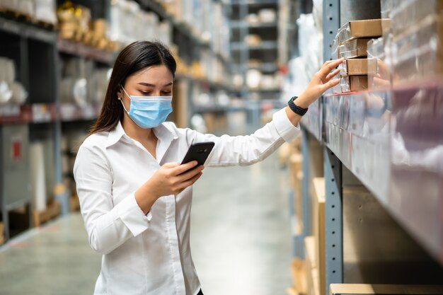 Woman worker with medical mask using smartphone to check inventory in the warehouse during coronavirus pandemic