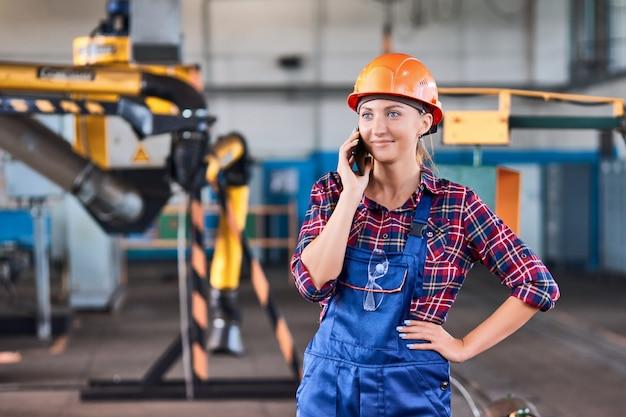 전화에서 찾고 산업 공장에서 하드 모자와 여성 노동자. 개념 게으른 노동자.