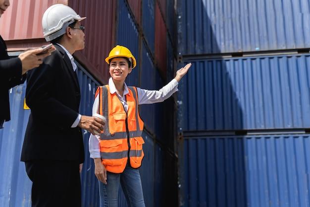 Женщина-работник, работающая с бригадиром, стоит с посудой в желтом шлеме для контроля погрузки и проверки качества контейнеров с грузового грузового судна для импорта и экспорта на верфи или в гавани