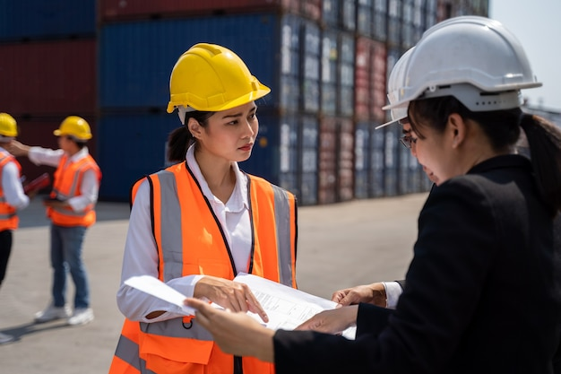 Woman worker working with foreman, standing with ware a yellow helmet to control loading and check a quality of containers from cargo freight ship for import and export at shipyard or harbor