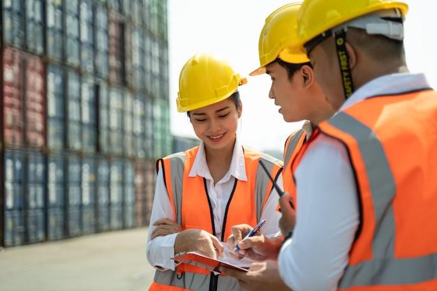 그녀의 동료와 함께 일하는 여성 노동자, 노란색 헬멧을 도자기와 함께 서서 선적을 제어하고 조선소 또는 항구에서 수입 및 수출을 위해화물 화물선에서 컨테이너의 품질을 확인합니다.