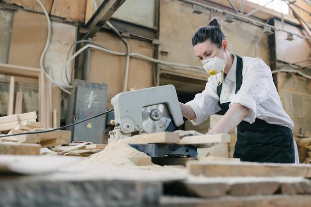 Женщина работает плотником в собственном столярном цехе с лесопилкой