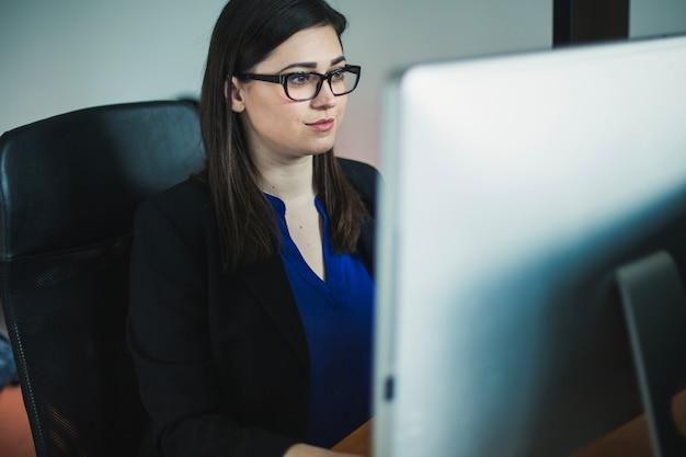 Женщина, работающая на компьютере в офисе