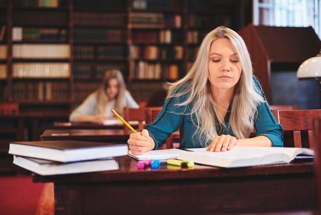 Женщина, работающая за столом, делая заметки