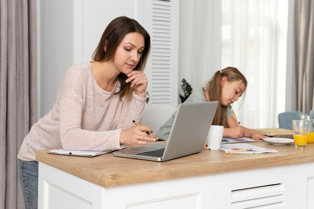 子供と一緒に机で働く女性
