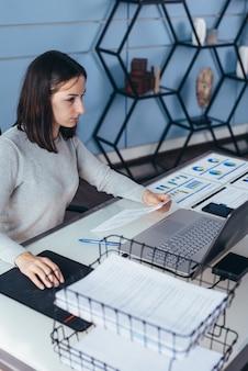 ドキュメントとラップトップで彼女のオフィスの机で働く女性。