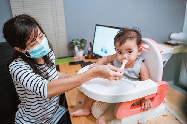 Женщина работает дома и заботится о своем ребенке