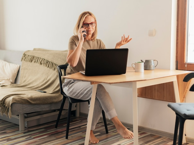 ノートパソコンとスマートフォンで検疫中に自宅で働く女性