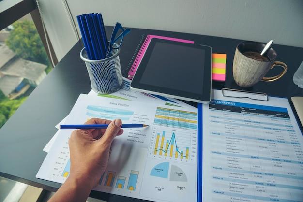 Женщина, работающая на домашнем офисном столе, используя диаграмму финансового документа дела ноутбука и диаграмму на деревянном столе с чашкой кофе. женщина-фрилансер читает отчет о продажах бизнес-графиков на офисном столе