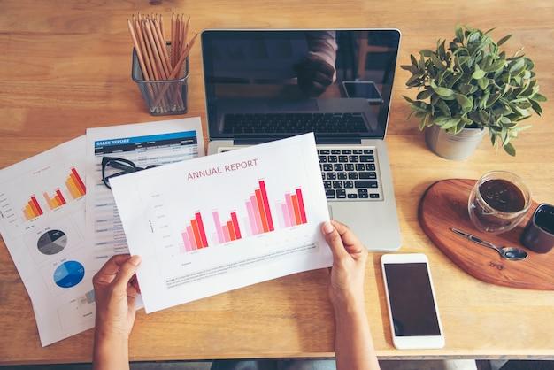 노트북 비즈니스 재무 문서 차트 및 그래프를 사용하여 홈 오피스 책상에서 일하는 여성