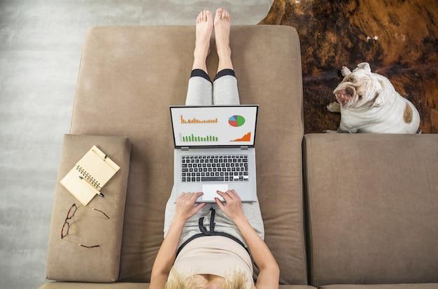 컴퓨터, 소파, 애완 동물 옆에 앉아 영어 불독에 집에서 일하는 여자.