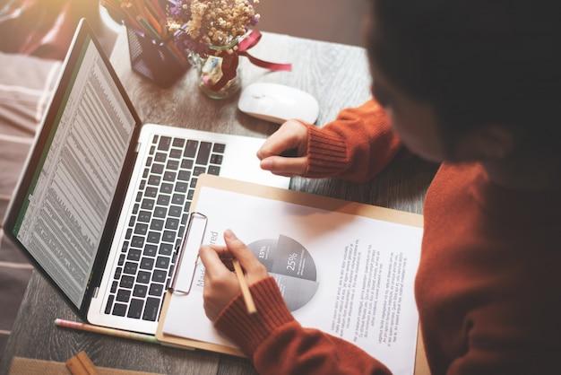 Женщина работает на дому, используя портативный компьютер для анализа бизнес-отчета - работа из дома концепции