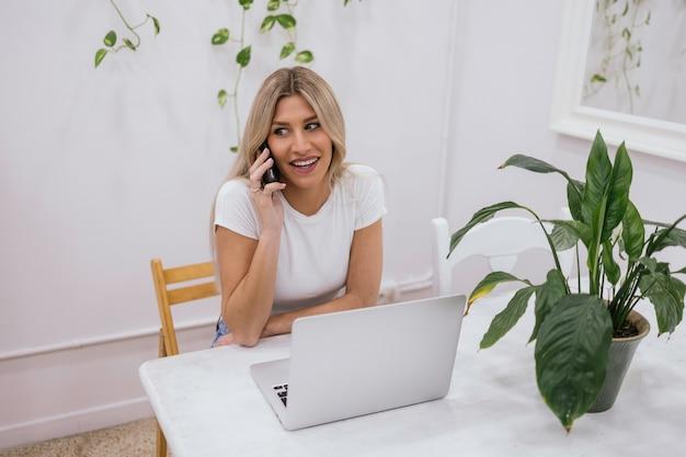 ノートパソコンとモバイルで在宅勤務の女性