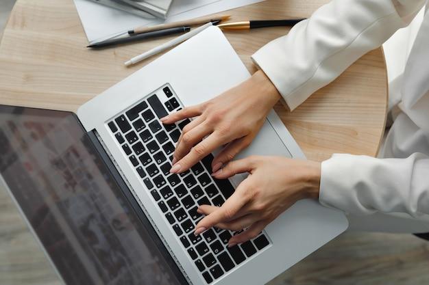 노트북 컴퓨터에서 일하는 여자 손을 닫습니다. 키보드에 손을 가까이 노트북에 바쁜 입력 여성 손의 근접 촬영. 재택 근무. 격리 및 사회적 거리두기 개념.