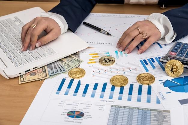 Женщина, работающая в офисе - ноутбук бизнес граф биткойн и доллар