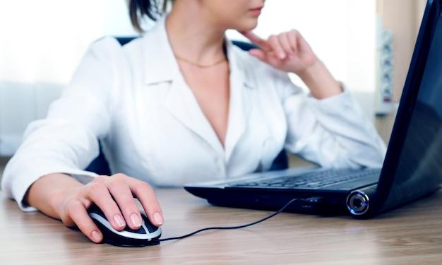 Женщина, работающая в офисе, рука на мыши крупным планом